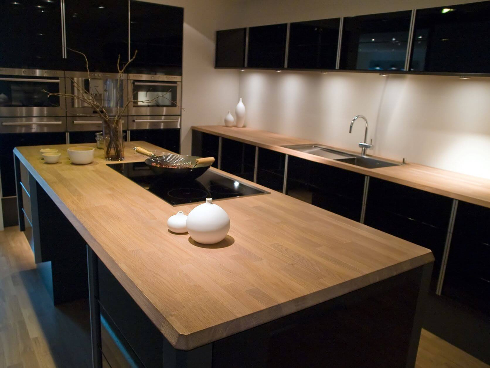 trendy kitchen with natural wood island and black hi gloss cabinets